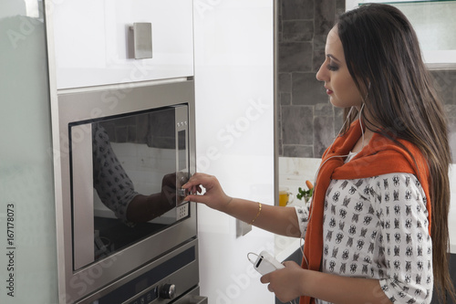 Young woman adjusting temperature of oven