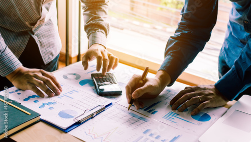 Fototapeta Two businessman team calculate about summary report annual on table office. obraz