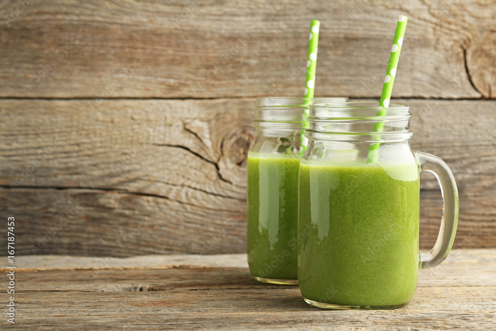 Fototapeta Bottles of juice with cucumber, celery and broccoli on grey wooden table