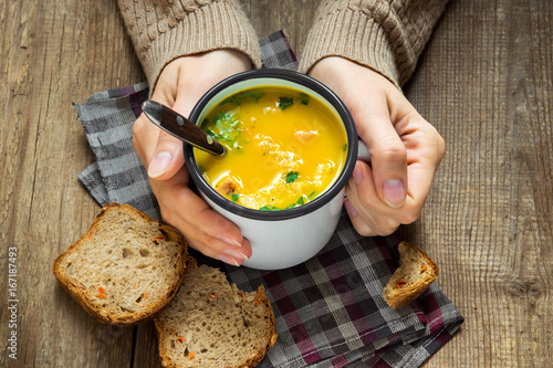hands holding mug of soup