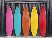 Colored Surfboards Leaning Up Against A Wooden Fence