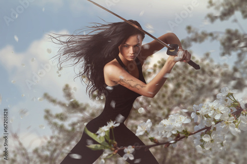 Foto  Beautiful Brunette with katana sword in spring floral environment