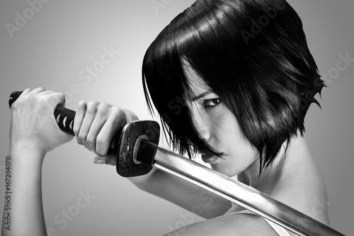 Fotografie, Obraz  Anime stylized brunettewith short hair watching with stern look holding a katana