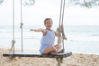 Happy child girl laughing and swinging on a swing at the beach