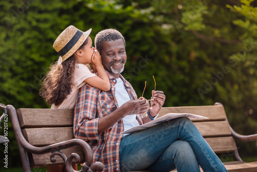 Obraz little adorable african american grandchild whispering to her smiling grandfather while sitting on bench in park - fototapety do salonu