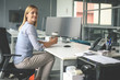 Business woman sitting in office. Woman having pause in work. Looking at camera.