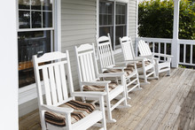 USA, Bangor, Maine. A Row Of Traditional White Rocking Chairs At The Porch Of An Inn.