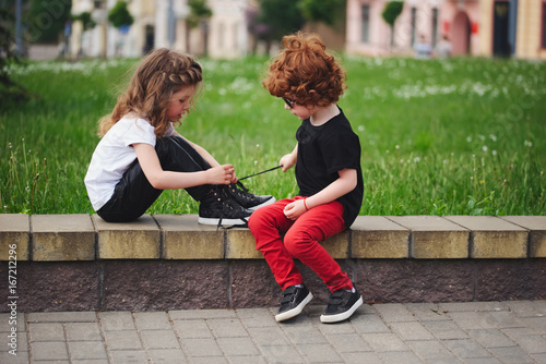 Fotografía  boy helps little girl tie shoelaces