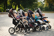 Funny Children Sitting In Strollers In Park