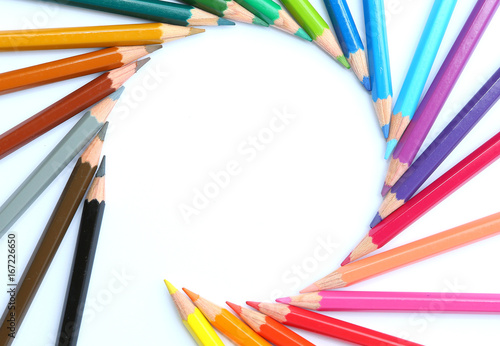 Photo colored pencils row with wave on white background.