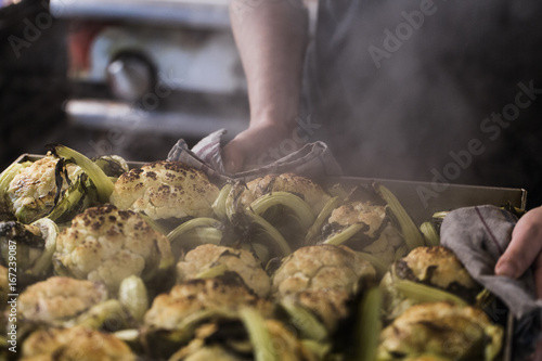 Chefs hand holding a metal tray with whole roasted cauliflowers