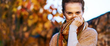 Young Woman Hiding In Scarf In Autumn Evening
