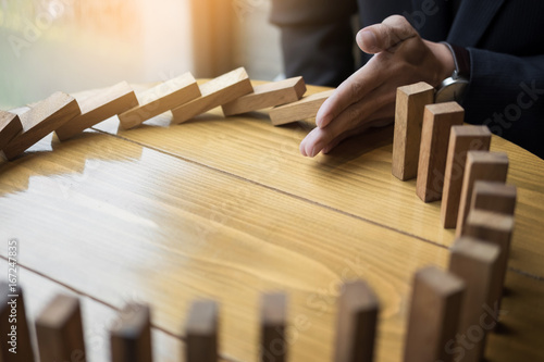 Fotomural businessman hand stop dominoes continuous toppled or risk with copyspace