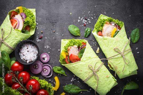 Fotografie, Obraz  Green spinach tortilla with chicken and vegetables on black slate table