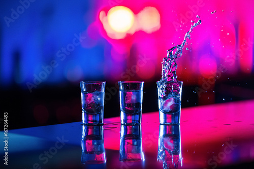A glass of vodka with ice on the bar, on a red background Poster Mural XXL