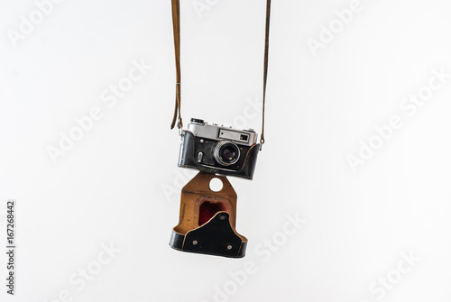 Fotografía  Vintage film camera in a leather case hanging on straps on a white background