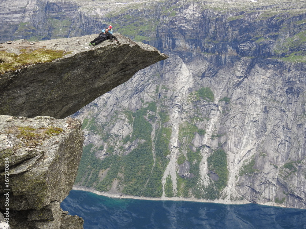 Fototapeta Couple sitting on a spectacular cliff