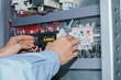 Electrician specialist checking low-voltage cabinet equipment