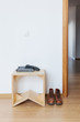 White empty anteroom with wooden stool and leather boots