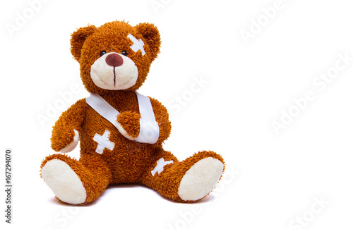 Injured teddy bear on white background
