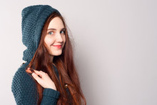 Attractive Attractive Woman In A Warm Knitted Sweatshirt With A Hood Coquettishly Holds A Strand Of Hair In Her Hands And Smiles.