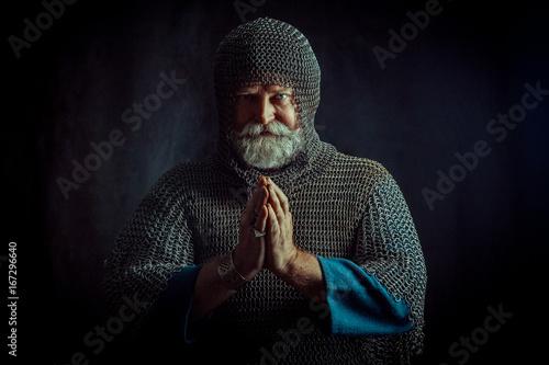 Fotografie, Obraz  Portrait of praying Templar knight on a dark background.