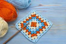 Crochet Handmade Granny Square, A Hook And Yarn Balls. The Beginning Of Bright Plaid, Blanket. Colorful Original Crochet Handmade Craft Work. Homemade Creative Craft.