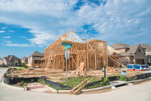 Stick Built Home Under Construction And Blue Sky In US. Suburban Neighborhood Home On Street Corner Lot Subdivision Next To Completed House. Pile Of Sand, Gravel, Log In Front. Industrial, Real Estate
