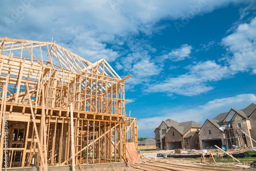 stick built home under construction and blue sky in US. Framing ...