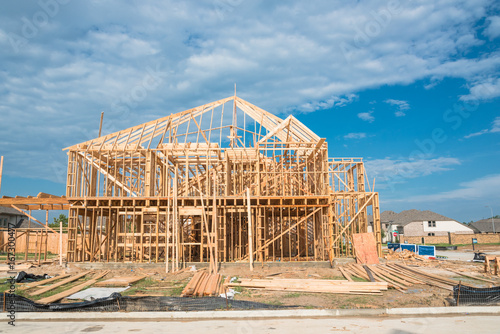 New stick built home under construction and blue sky in US. Framing ...