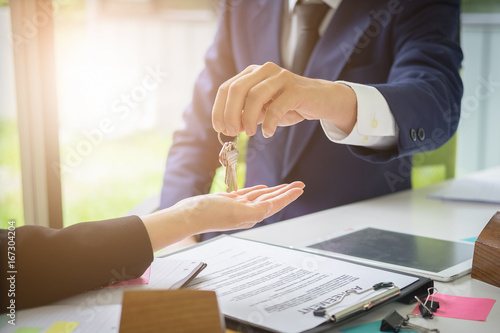 Agents are giving house keys of customer and holding dollar us bank at agency office Canvas Print