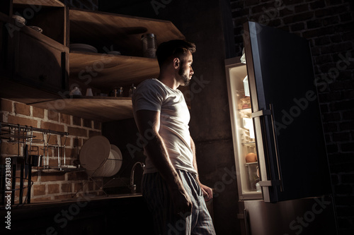 Fotografie, Obraz  side view of bearded young man in pajamas looking at open refrigerator at night