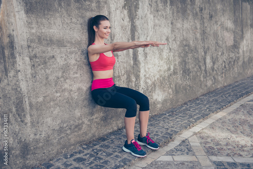 Young fashionable sportswoman is stretching on the street on a summer day Wallpaper Mural