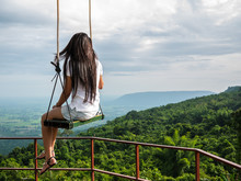 Lonely Woman Sit On Handmade Swing On The Tree At Top Of Mountain With Landscape Background, Lonely And Looking For Something