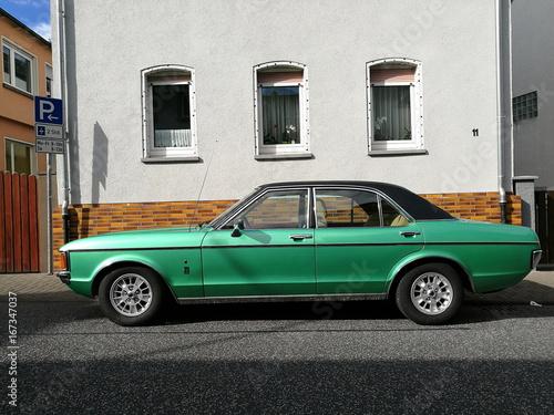 Foto  Grüne viertürige Limousine der Siebzigerjahre mit schwarzem Vinyldach bei den Go