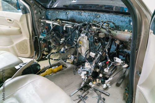 Photo interior view of a car repair & electric wiring system showing wires in a car,
