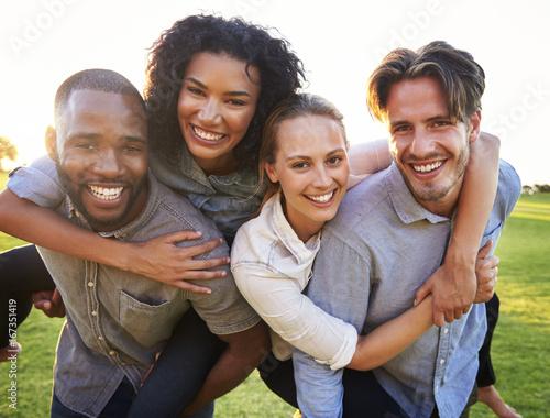 Fotografía  Two young couples having fun piggybacking outdoors