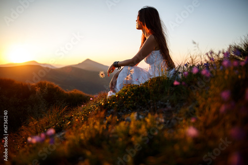 Poster Marron chocolat Beautiful woman in a long white dress in the mountains. Young woman sitting on a rock. Hair blowing in the wind