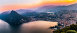 canvas print picture - Aerial view of the lake Lugano surrounded by mountains and evening city Lugano on during dramatic sunset, Switzerland, Alps. Travel