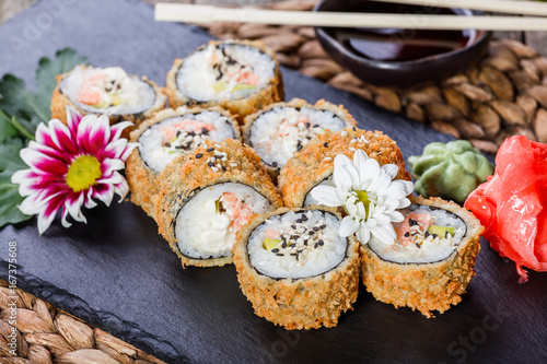 Photo Hot fried Sushi rolls and maki set with Crab Meat, cream cheese, avocado and wasabi on black stone on bamboo mat, selective focus