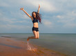 Happiness young Girl jumping on the beach