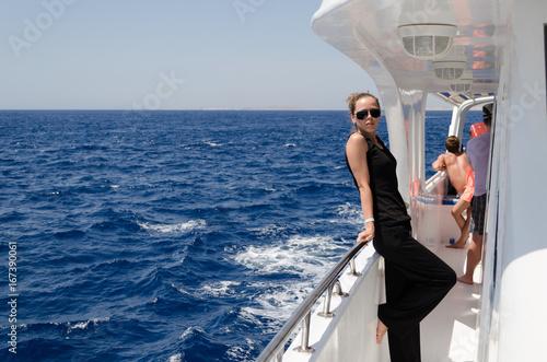 Plakat Dziewczyna w ciemnych ubraniach i okularach spoczywa na białym jachcie