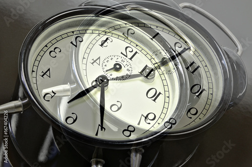Breakdown of Time / close up of   two, overlapping images with  retro alarm clocks, showing different times, horizontal, slanted