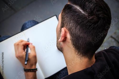 Student notiert Gedanken in ein Notizbuch Wallpaper Mural