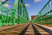 Green Metal Bridge Over River With Nineteenth Century Brick Mill Buildings In Background
