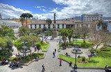 High view of the Independence Plaza in downtown Quito, with the independence monument, trees, gardens and people on a sunny morning. Quito, Pichincha, Ecuador.