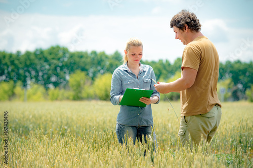 Photo Farmer and agronomist discussing about future crop of wheat, at the field