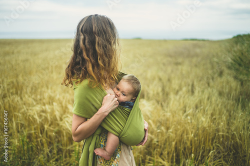 Fotografía Mother breastfeeding baby in field