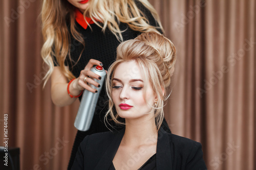 Fotografie, Obraz  Closeup view of a hairdresser coiffeur makes evening hairstyle to the blond mode