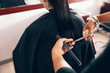 Hairdresser trimming a woman's hair at salon